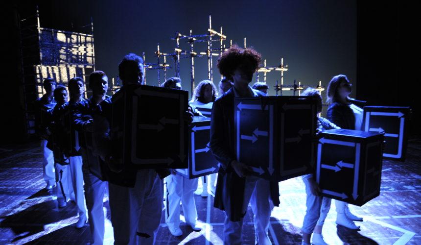 Gli attori mantengono dei cubi sul palco durante la rappresentazione