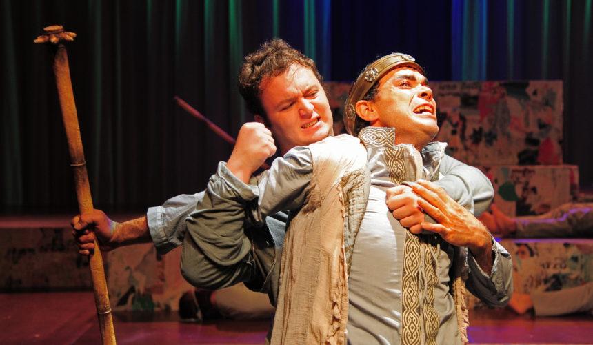 Personaggio afflitto al dolore viene trattenuto, rappresentazione degli attori sul palco